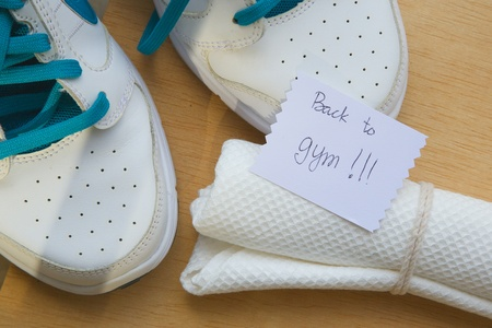 gripper: Message written on a piece of paper: \Back to gym.\ Sport items background: snickers,jumping rope,white towel, hand gripper.