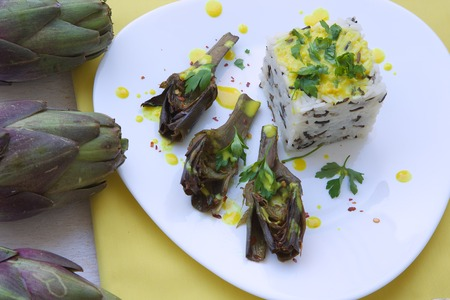 curcumin: Healthy vegetarian lunch: oven baked violet artichokes with mixed wild rice and yellow sauce. Top view Stock Photo