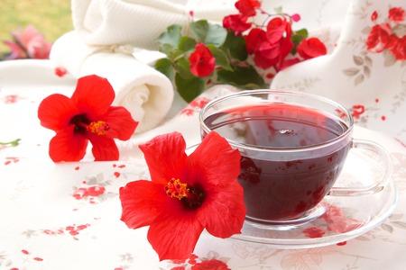 elasticidad: Una taza vaso de t� de hibisco. Flores de hibisco en el fondo.