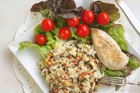 Centrum obiad: kurczak ryż z świeżych liści sałaty, pomidorów cherry i szklanką świeżego soku z cytryny na białym powierzchni drewnianych