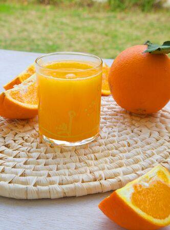 woven surface: Un vaso de zumo de naranja natural en una superficie tejida. Naranjas frescas en el fondo Foto de archivo