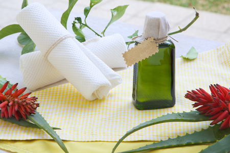 A glass bottle of aloe vera oil. White towels  and fresh aloe vera in the background photo