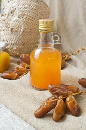 intestinal cancer: Dates vinegar in glass bottle. Twigs with dates in the background Stock Photo