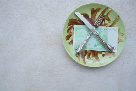consummation: Money, fork,knife are placed on a dirty green plate. Free space for a text Stock Photo