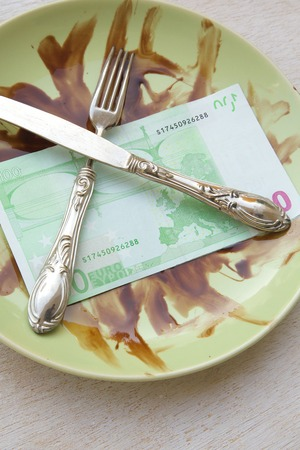 Money, fork,knife are placed on a dirty green plate.
