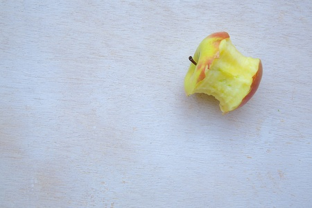 explored: An eaten apple on a white wooden surface Stock Photo