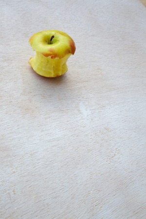 consummation: An eaten apple on a white wooden surface. Free space for a text