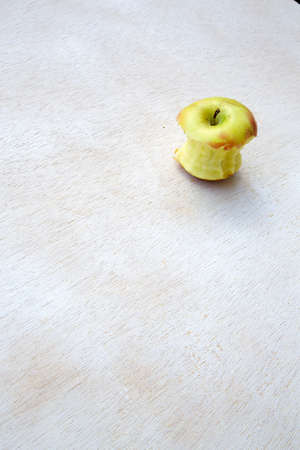explored: An eaten apple on a white wooden surface. free space for a text, Stock Photo