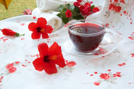 herbal knowledge: A glass cup of hibiscus blossoms herbal tea. Hibiscus blossoms in the background. Stock Photo