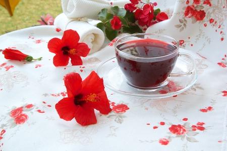elasticidad: Una taza de cristal de flores de hibisco t� de hierbas. Flores de hibisco en el fondo.