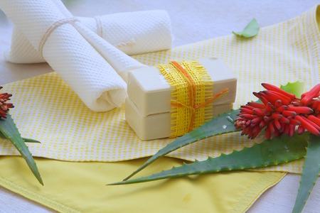 Aloe vera soap. Aloe vera and white towels on a yellow napkin in the background photo