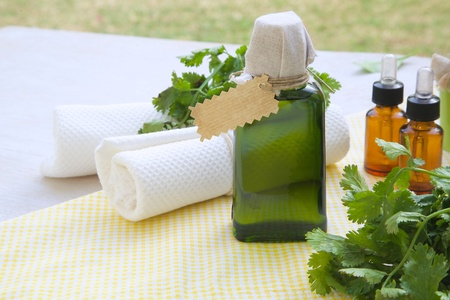 A glass bottle of coriander oil on yellow napkin. Free space for a text photo