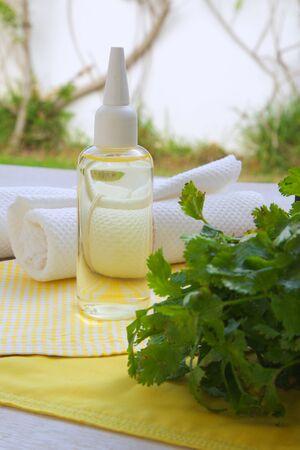 pain killer: Coriander hair oil on yellow napkin Stock Photo