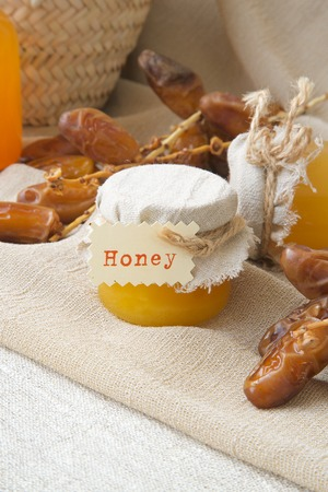 intestinal cancer: Dates honey in small glasses. Twigs with dates in the background