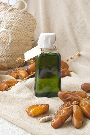 intestinal cancer: A glass bottle of dates seeds oil. Dates  in the background