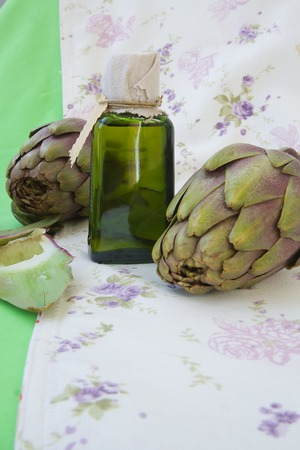 intestinal cancer: A glass bottle of artichoke oil. Artichokes in the background