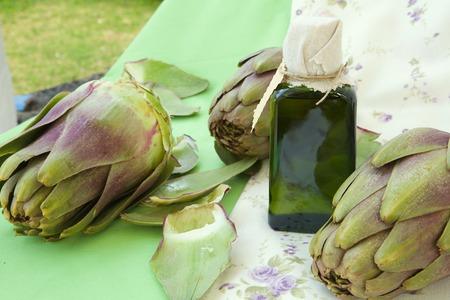 gallstones: A glass bottle of artichoke oil. Artichokes in the background