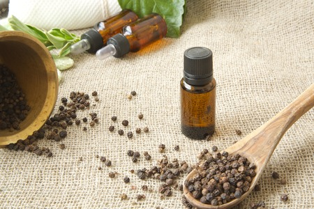 essential oil: A dropper bottle of black pepper essential oil. Black pepper in the background.