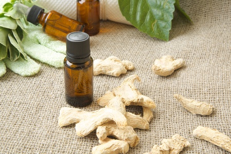 A dropper bottle of ginger root essential oil. Dried ginger root in the background on sackcloth. Free space for a text