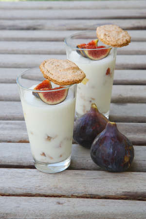 anti oxidants: Ricotta cheese dessert with fresh pieces of fig and crispy homemade biscuits. The dessert and two fresh violet figs on a wooden surface Stock Photo