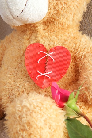 repaired: Repaired broken red heart on the chest of Teddy bear. Stock Photo