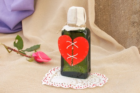repaired: Repaired broken red heart on a green glass bottle. Closeup