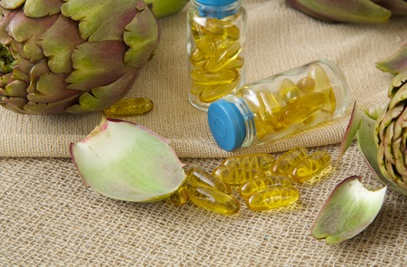 intestinal problems: Artichoke oil softgels on a sackcloth