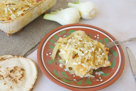 bread mold: Healthy vegetarian dinner: oven baked fennel with potatoes and cheese. Glass mold with a dinner , small Lebanese bread, fresh fennel bulbs,fork and a knife.