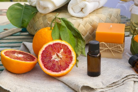 limonene: A dropper bottle of blood orange essential oil. Spa products in the background. Stock Photo