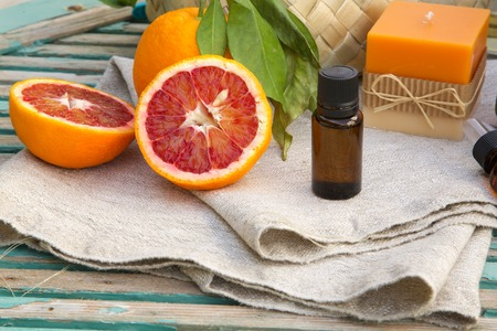 A dropper bottle of blood orange essential oil. Spa products in the background. Stock Photo