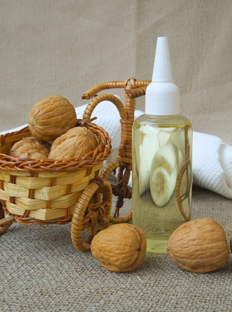Hair serum with walnut oil. Walnuts in woven bicycle in the background.