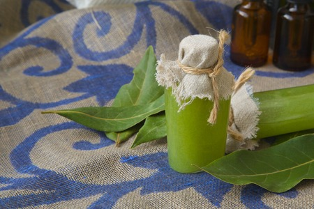 antispasmodic: A bottle of bay leaf body scrub. Bay leaves in the background