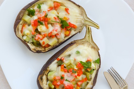 ovenbaked: Healthy vegetarian lunch: oven-baked stuffed aubergines with vegetables and cheese on a white plate.