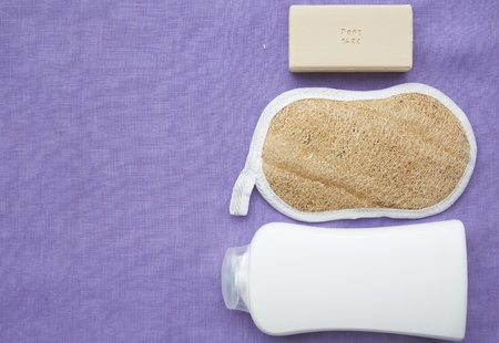personal hygiene: Personal hygiene items on a violet fabric: shower gel,bath sponge,a bar of soap. Background Stock Photo