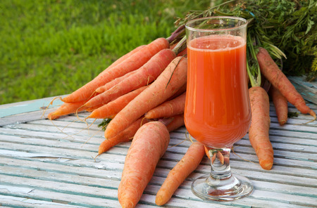 lycopene: A glass of fresh carrot juice on a wooden surface. Fresh carrots in the background. Free space for a text Stock Photo
