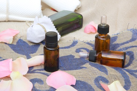 erectile: A dropper bottle of rose essential oil. Rose petals in the background