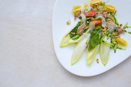 escarola: Ensalada de la vitamina invierno: escarola, r�cula, at�n, nueces de madera de cedro, tomates cherry, queso parmesano, pepino. Fondo. Espacio libre para el texto
