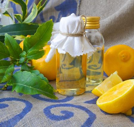 aroma facial: A bottle of bergamot oil. Bergamot fruits in the background. Stock Photo