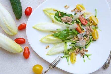 escarola: La vitamina ensalada: escarola, r�cula, at�n, nueces de madera de cedro, tomates cherry, queso parmesano, pepino. Fondo Foto de archivo