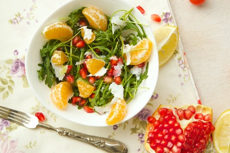 Fitness salad with tangerines,rucola leaves,pomegranate grains,olive oil, and parmesan cheese.Fork and a knife on a sackcloth. Top view