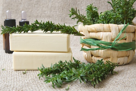 Soap with summer savory essential oil. Plant twigs in the background Stock Photo