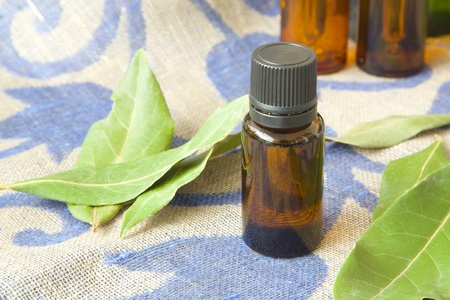 relaxant: A dropper bottle of bay leaf essential oil. Bay leaves in the background