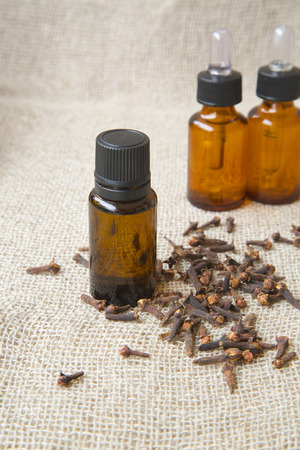 ejaculation: A dropper bottle of clove essential oil. Clove buds in the background.