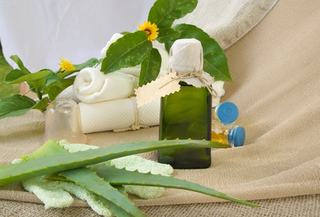 A glass bottle of aloe vera oil. White towels in the background