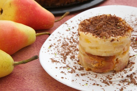 kin: A piece of  cheese cake with chocolate chips,lemon skin and pomegranate grains on a white plate. Fresh pears in the background. Closeup Stock Photo