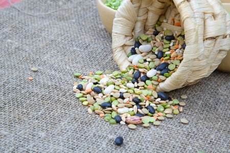 free dish: An assortment of dried legumes and cereals in brown woven dish on sackcloth: green peas,pearl barley,wheat,green and orange lentils,red French beans,black beans. Free space for a text Stock Photo