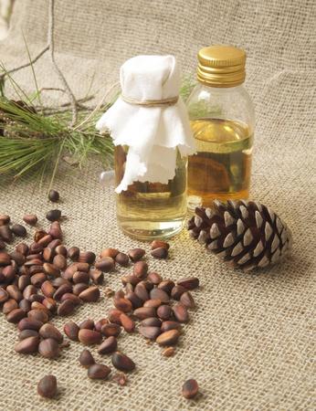 antispasmodic: A glass of cedar wood oil. Cedar wood nut in the background