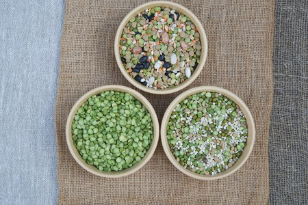muscle fiber: An assortment of dried legumes and cereals in brown clay dishes on sackcloth: green peas,pearl barley,wheat,green and orange lentils,red French beans,black beans