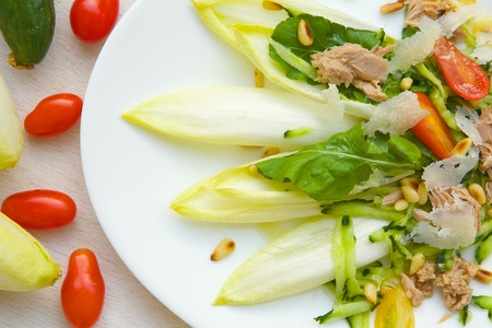 escarola: La vitamina ensalada: escarola, rúcula, atún, nueces de madera de cedro, tomates cherry, queso parmesano, pepino. Fondo Foto de archivo