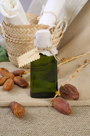 intestinal cancer: A glass bottle of dates seeds oil. Dates in the background.